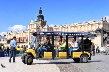 Krakow , Republic of Poland- July 3, 2017:  A car for ekkursiy through the ancient Krakow on Main Market Square. Krakow , Republic of Poland- July 3, 2017:  A car for ekkursiy through ancient Krakow on the streets of the city.