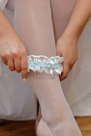 Photo for Bride puts on a blue garter and empty space for text - Royalty Free Image