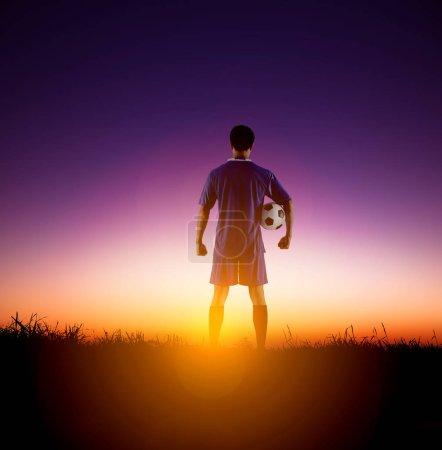 Photo pour Vue arrière footballeur regardant le lever du soleil - image libre de droit