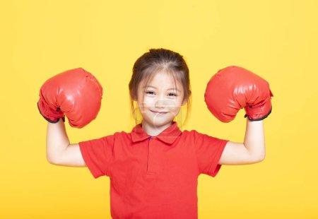 Foto de Niña feliz con guantes de boxeo rojos sobre fondo amarillo - Imagen libre de derechos