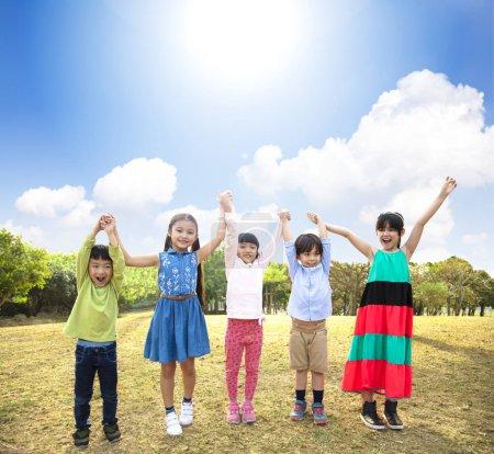 Photo pour Heureux Groupe multi-ethnique d'écoliers dans le parc - image libre de droit