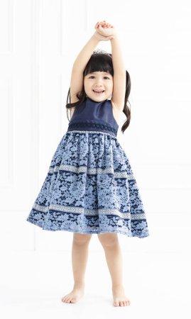 Photo pour Heureuse petite fille se tient sur fond blanc - image libre de droit