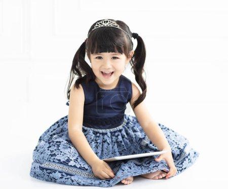 Photo pour Heureuse petite fille assise sur fond blanc - image libre de droit