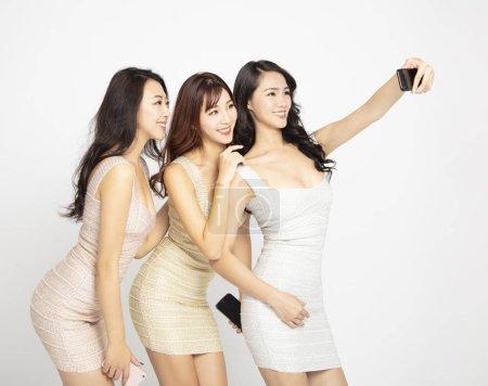 Photo pour Trois jeune beauté prendre selfie avec smartphone - image libre de droit