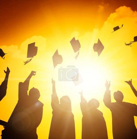 Photo pour Étudiants heureux jetant des casquettes de graduation dans l'air - image libre de droit
