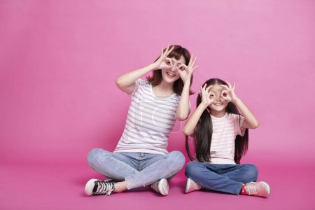 Photo for Happy mother and daughter holding fingers near eyes - Royalty Free Image
