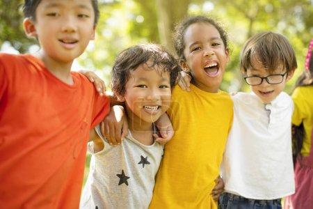 Groupe multi-ethnique d'écoliers riant et embrassant