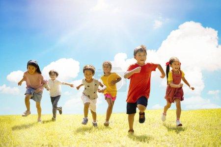 Photo pour Groupe multi-ethnique d'écoliers riant et courant - image libre de droit