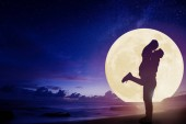 young couple kissing on beach and watching the moon.