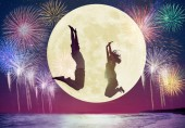 young couple jumping on beach and watching the moon.Celebrate Mi