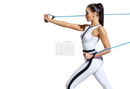 Photo for Strong woman performs exercises for the muscles hands with resistance band. Photo of fitness model in fashionable sportswear isolated on white background. Strength and motivation. Copy space - Royalty Free Image