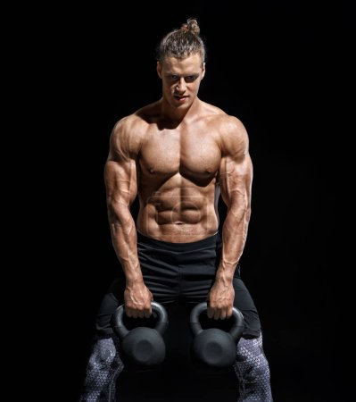 Photo for Young athletic man working out with a kettlebells. Photo of strong male with naked torso on black background. Strength and motivation - Royalty Free Image