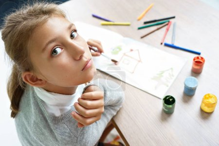 Photo pour Dessine une fille solitaire. Photo d'écolière mignon à faire leurs devoirs. Concept de l'éducation - image libre de droit