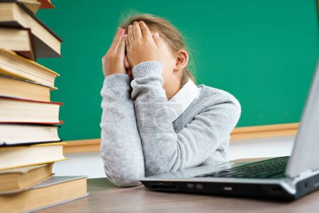 Photo for Schoolgirl closed her eyes and crying. Photo of little girl in classroom around books. Education concept - Royalty Free Image