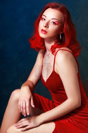 portrait of beautiful purple red haired girl with fantasy flame make-up in red dress