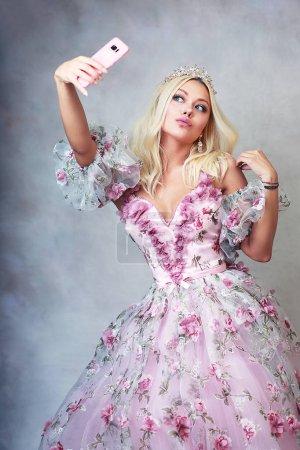 Photo pour Belle princesse en robe rose avec dentelle et roses faisant selfie - image libre de droit