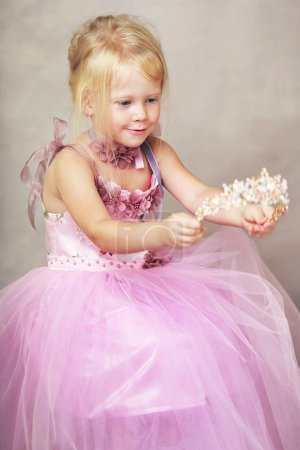 Photo for Beautiful little princess in rosy pink gown dress and crystal crown - Royalty Free Image