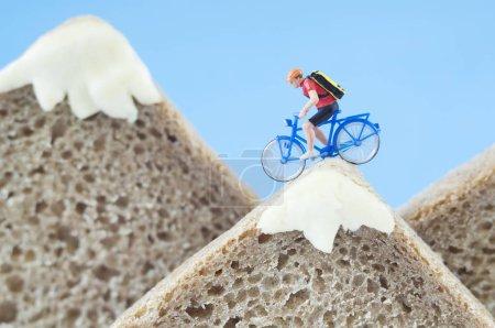 Photo pour Un cycliste jouet fait une balade en montagne, faite de pain de seigle et de fromage crémeux. Écotourisme et saine alimentation concept . - image libre de droit