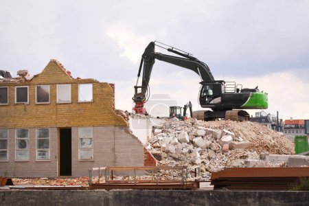 Demolition of building with caterpillar at construction site