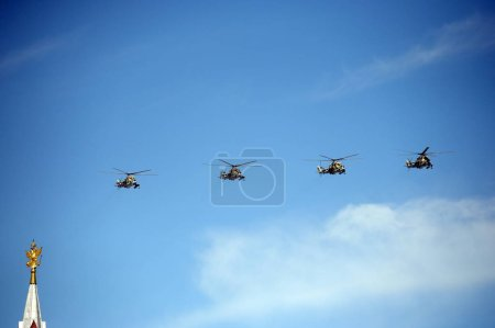 Shock-and-combat helicopters Mi-24P during the parade fly in the sky over Red Square.