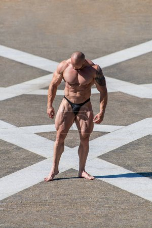 Photo for Powerful muscular bodybuilder in panties posing at the park. Quadriceps contraction - Royalty Free Image