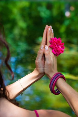 Photo pour Femme mains avec fleur dans yoga mudra geste en plein air dans la nature gros plan jour d'été - image libre de droit