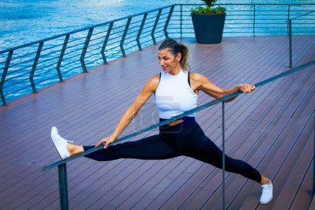 Photo for Smiling woman middle-aged fitness instructor workout outdoor summer day city promenade along river - Royalty Free Image