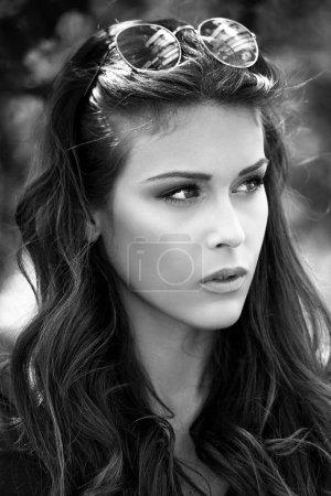 Photo pour Noir et blanc portrait de jeune femme urbaine avec des lunettes de soleil dans les cheveux journée d'été en plein air gros plan - image libre de droit
