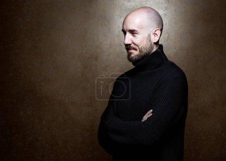 Photo pour Portrait de mode d'un homme de 40 ans debout sur un fond gris clair dans un pull noir. Ferme là. Style classique. Tête rasée chauve. Espace de copie. Plan studio - image libre de droit