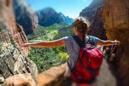 Photo pour Femme randonneuse debout avec les mains levées et profite de la vue sur la vallée dans le parc national de Zion, États-Unis - image libre de droit