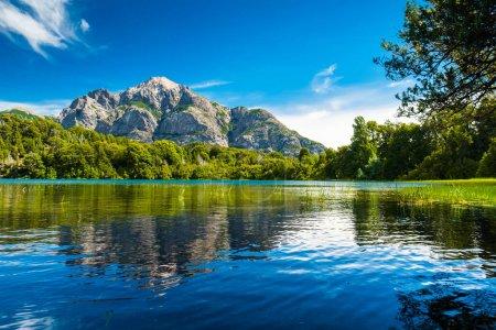 Photo pour Lac avec de l'eau claire herbe verte sur la côte et reflété montagne. Argentine - image libre de droit