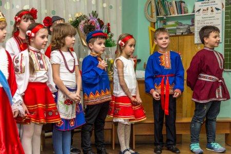 Foto de Odessa, Ucrania - 04 de marzo de 2016: grupos de música de niños cantando y bailando en la celebración del día de la mujer. Día de las madres. Los niños pequeños están felicitando el 8 de marzo. Emocional, tocar el show musical de la etapa de infantil. - Imagen libre de derechos