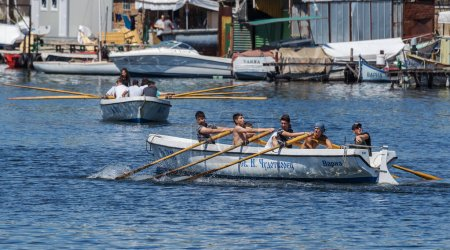 VARNA, BULGARIA - CIRCA 2017: Young athletes train in a rowing team on marine lifeboats in the water area of the port of Varna