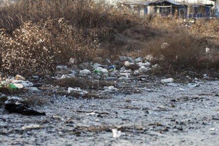 Photo pour Déversement d'ordures sur la plage d'une grande ville. Vide utilisé des bouteilles de plastique sales. Côte de la mer sale, sable de la mer noire. Pollution de l'environnement. Problème écologique - image libre de droit