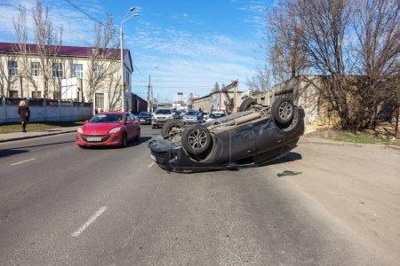 Photo pour Odessa, Ukraine 19 mars 2019: après l'accident de voiture, voiture a capoté et coucha sur toit sur route cet autre lecteur de voitures. Concept de la conduite imprudente, enfreindre les règles et excès de vitesse sur route - image libre de droit