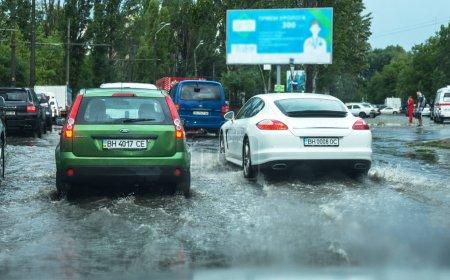 Photo pour Odessa, Ukraine - 9 août 2019 : conduite d'une voiture sur une route inondée lors d'inondations causées par des pluies torrentielles. Les voitures flottent sur l'eau, inondant les rues. Splash sur la voiture. Route de ville inondée avec une grande flaque - image libre de droit