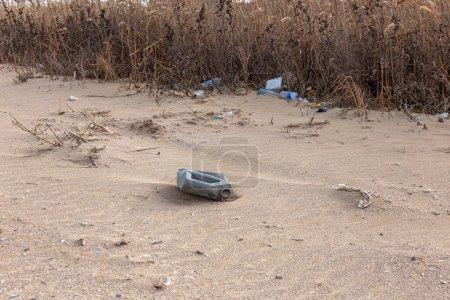 Photo pour Les touristes et les vacanciers laissent les ordures coulées sur la côte de la mer. Mer sale rivage sablonneux de la mer. Pollution de l'environnement. Le problème environnemental a un impact négatif. Vide utilisé bouteilles en plastique sale - image libre de droit