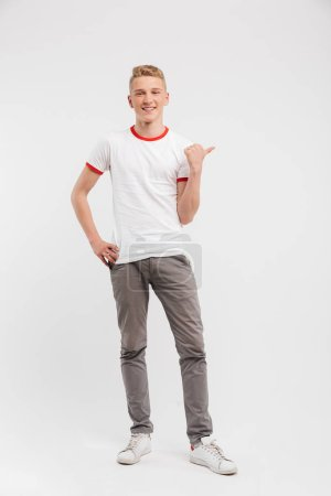 Photo for Full length portrait of a happy teenage boy pointing at copy space isolated over white background - Royalty Free Image