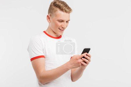 Photo pour Photo d'un jeune homme moderne portant des vêtements décontractés tapant ou faisant défiler les réseaux sociaux sur un téléphone cellulaire isolé sur fond blanc - image libre de droit