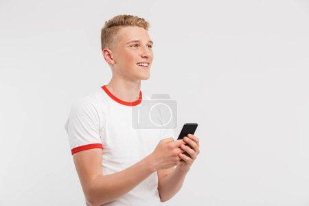 Photo pour Photo d'un jeune joyeux portant des vêtements décontractés tapant ou faisant défiler les réseaux sociaux sur un téléphone cellulaire isolé sur fond blanc - image libre de droit