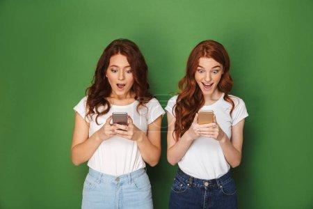 Photo pour Portrait de deux femmes rousse excitée 20 ans se présentant à la caméra et à l'aide de smartphones isolé sur fond vert - image libre de droit