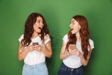 Photo pour Portrait de deux adolescentes aux cheveux roux se regardant et utilisant des téléphones cellulaires isolés sur fond vert - image libre de droit