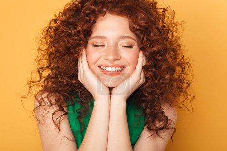 Bouchent portrait d'une femme rousse bouclés souriant avec les yeux fermés isolé sur fond jaune
