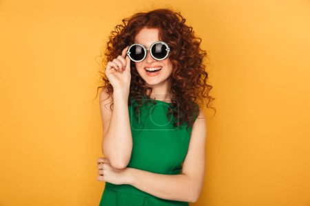 Portrait of a happy redhead woman in dress and sunglasses isolated over yellow background