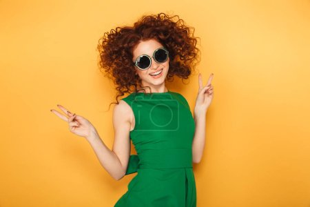 Portrait of an excited redhead woman in dress and sunglasses celebrating success isolated over yellow background