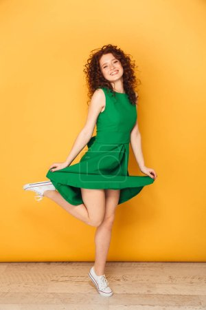 Full length portrait of a happy redhead woman in dress posing while jumping isolated over yellow background