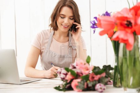 Young cute cheerful florist lady over flowers in workshop talking by mobile phone writing notes.