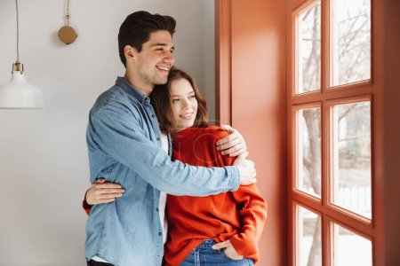 Lovely young couple hugging while standing together indoors and looking at the window