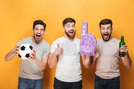 Three young excited men football fans celebrating isolated over yellow background