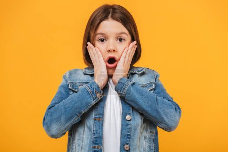 Portrait of a surprised little schoolgirl looking at camera over yellow background